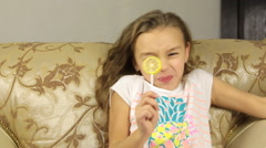 Girl licking candy on a stick in the form of lemon she was very sour Stock Footage