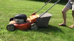 Peasant woman in flip-flop shoes walk push lawn cutter mower machine. 4K Stock Footage