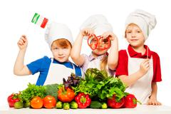 Three young cooks preparing Italian meal - stock photo