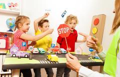 Cute kids having fun teaching traffic signs Stock Photos