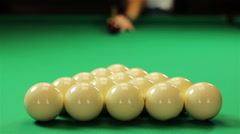 Red ball hitting white balls in triangle at start of billiard game Stock Footage