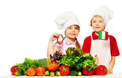 Young Italian cooks preparing fresh salad - stock photo