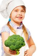 Smiling girl in cook's uniform with broccoli Stock Photos