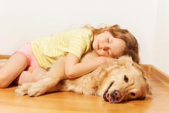 Sleeping little girl lying on her Golden Retriever Stock Photos