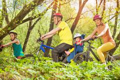 Sporty family running bikes in the sunny forest Stock Photos