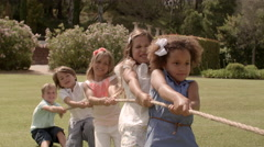 Five children pulling rope having tug of war in park Stock Footage