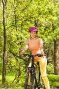 Female cyclist enjoying spring forest view - stock photo