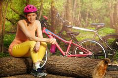 Active woman relaxing after cycling sitting on log - stock photo
