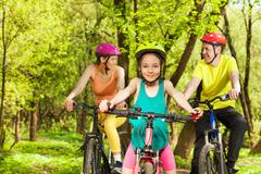 Happy girl having fun the cycling with her parents Stock Photos