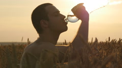 Boy having water break at sunset. The Sun in the Background. Silhouette Stock Footage