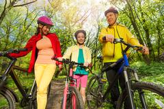 Active family with mountain bikes walking in park Stock Photos
