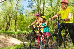 Happy cyclists admiring landscape of spring park - stock photo