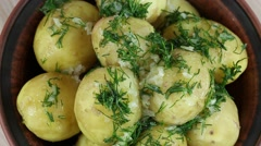 Boiled potatoes with dill and garlic in butter on a plate close up - stock footage