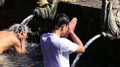 People come to sacred springs water temple Tirta Empul in Bali, Indonesia - stock footage