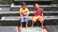 Happy two boy enjoys life on the street in Ubud, Bali, Indonesia Stock Footage
