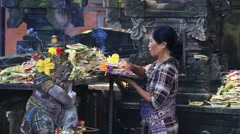 Women bring offerings of fruits and gifts to temple, Ubud, Bali, Indonesia Stock Footage
