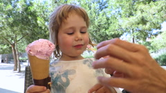 Little child eating strawberry ice cream cone front Stock Footage