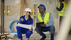 4K Architect or engineer having discussion with foreman at construction site Stock Footage