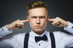 Closeup portrait of worried boy covering his ears, observing. Hear nothing Stock Photos