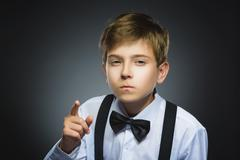 Portrait of displeased angry boy with threatens finger isolated on gray Stock Photos