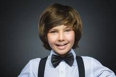 Happy child. Closeup Portrait of handsome boy smiling isolated on grey - stock photo