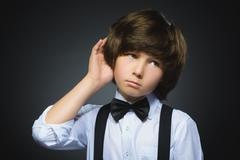 Doubt, expression and people concept - boy thinking over gray background Stock Photos