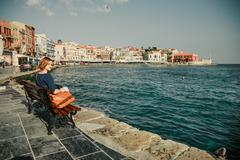 Young woman sitting on the  bench and looking at old port in Chania, Crete, G Stock Photos