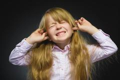 Closeup portrait of worried girl covering her ears, observing. Hear nothing Stock Photos