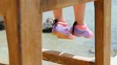Legs of little girl on sea background Stock Footage