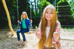Portrait of happy and smiling child show thumb up at park. On the background Stock Photos