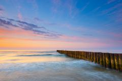 Sunset on the beach with a wooden breakwater, long exposure Stock Photos
