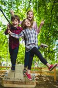 Smiling kids having fun at playground. Children playing outdoors in summer Stock Photos