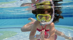 little girl swimming under water in the pool - stock footage