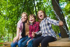 Smiling kids having fun at playground. Children playing outdoors in summer - stock photo