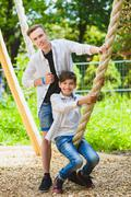 Smiling boys having fun at playground. Children playing outdoors in summer Stock Photos