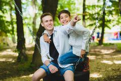 Smiling boys having fun at playground. Children playing outdoors in summer - stock photo