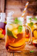 Peach ice tea in mason jar with mint Stock Photos