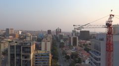 Luanda, Angola Panorama of city skyline with a crane and traffic on boulevard - stock footage