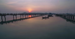 Sunset Over Boats Moored in a Bay Next to a Pier Ascending Approach Shot Stock Footage