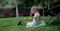 Little Girl Sitting on the Grass With Tablet pc and Watching Cartoons Stock Footage