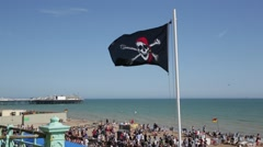 Pirate flag by the seaside in England Stock Footage