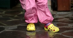 Feet of a Kid Jumping in Sandals Through Puddles Stock Footage