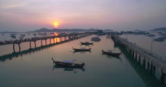 Chalong Bay in Phuket with Boats and Pier Sunrise Aerial Ascending Pullback Shot Stock Footage