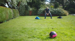 4K 2 Active young boys playing soccer with their father in the garden Stock Footage