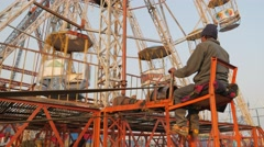 Man operating ferris wheel,Chitwan,Nepal Stock Footage