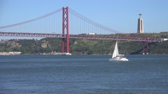 25th of April Bridge suspension bridge over river Tejo with Jesus Christ the Stock Footage
