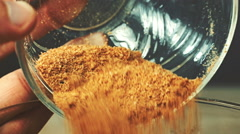 Close-up view of breadcrumbs and spices mixed together pours into a glass bow Stock Footage