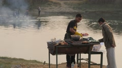 Men barbeque at river bed,Chitwan,Nepal - stock footage