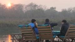 Men enjoying beer at river bed,Chitwan,Nepal - stock footage
