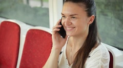 Woman talk to cell phone in the public transport, girl talking on the phone in - stock footage